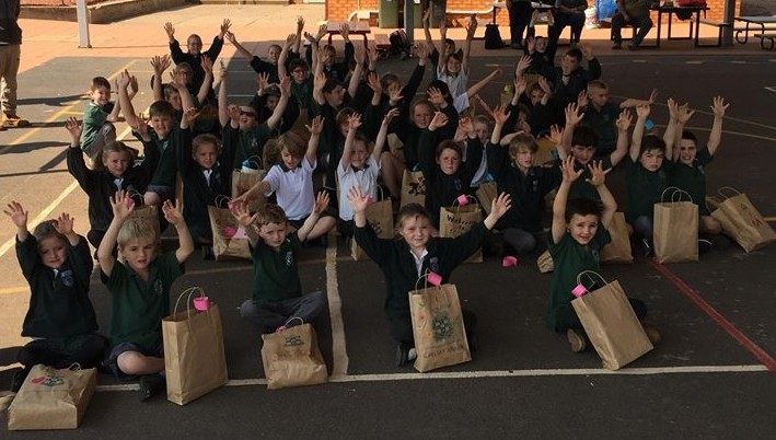 Tullamore junior students with their hands in the air after recieving their gift packs.